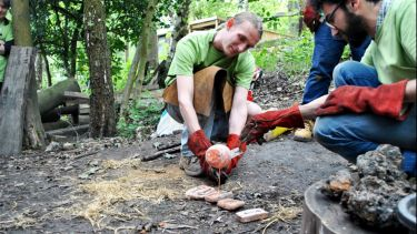 Two archaeology students recreating prehistoric metallurgy in a woodland environment.