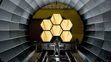 A worker looking at six hexagon mirrors in a space telescope.