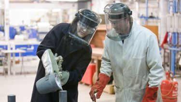 Engineering students wearing safety masks in a lab.