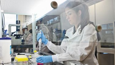Bioengineering student Erika Olavicino Lopes Ferreira working in the lab. She holds a pipette.