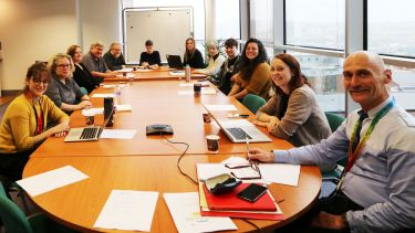 Photograph of Archaeology Strategic Board sat around a conference table