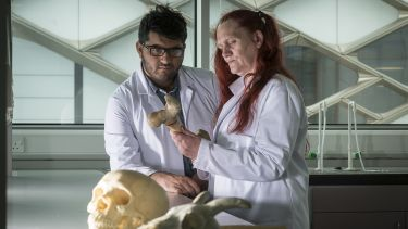 Two students in lab looking at a bone with skulls in background