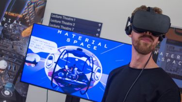 Man wearing virtual reality headset in front of an electronic display