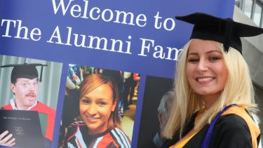 A female graduate stands in front of the alumni banner stand.
