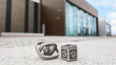 A modern building in the background, metal 3D-printed objects in the foreground