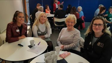 Four female attendees at the Dementia Cafe enjoying some coffee and tea.