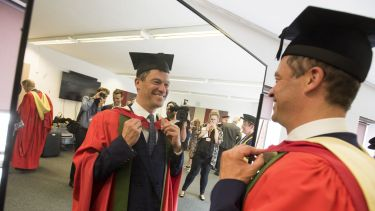 Honorary Graduate Dominic West looking in a mirror