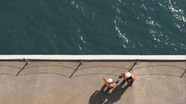 Overhead view of Caucasian technicians shaking hands near water