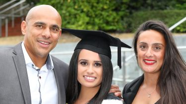 A graduate with her mum and dad. They are smiling.