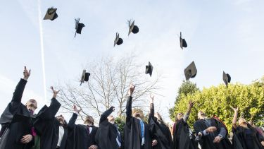 Graduates throw their hats on graduation day.