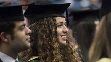 A female postgraduate graduate at the ceremony. She has long brown hair.