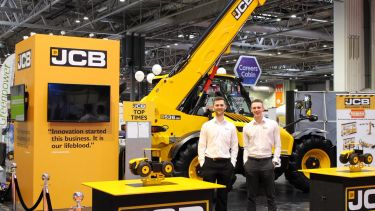 Year in Industry student James Holden at JCB in from of some JCB equipment.