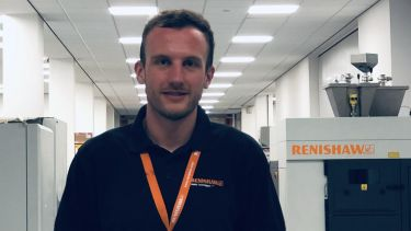 Year in Industry student James Wardle on placement. He has on a polo shirt and orange lanyard.