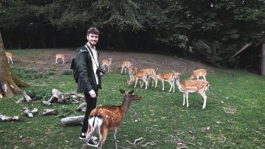 Joseph in a field of deer during his summer school
