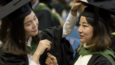 Two postgraduate students adjusting their robes and mortar boards at graduation.