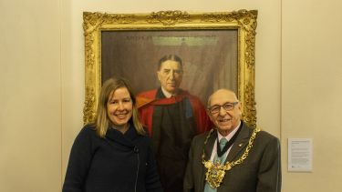 Dr Sally Hall and the Lord Mayor of Sheffield standing with a portrait of Sir Arthur