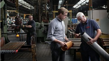 Two men looking at a pipe in a factory