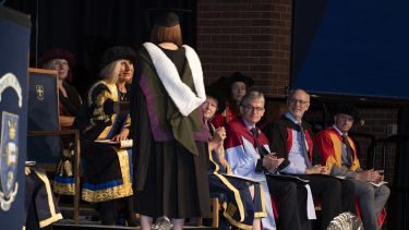 Graduand on stage shaking hands