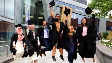 Happy graduands jumping in the air