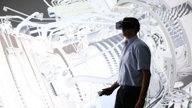 A man using a VR headset to examine a virtual turbine