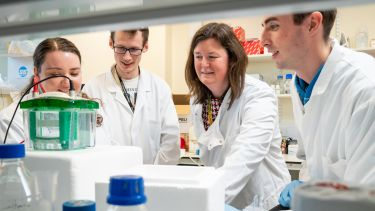 Dr Heather Mortiboys leading a team of Parkinson's researchers in a lab