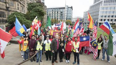 A group of students stood together holding the flags of countries from around the world.
