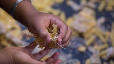 Photograph of child playing with pasta and straw