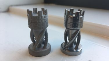 Two rook chess pieces, one 3D printed and sintered, one also polished to make it shiny