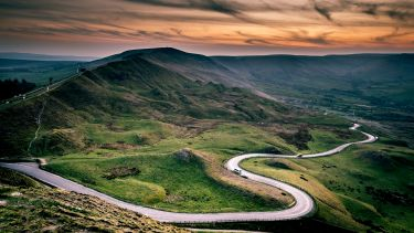 The winding road at Mam Tor. Mam Tor is green and grassy and the sky is red as if the sun is just starting to set.