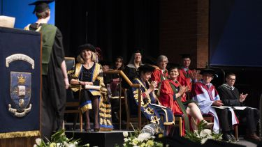 PG student shaking hands with chancellor on stage