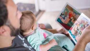 Photograph of father reading to baby