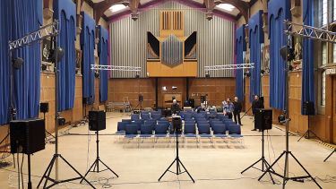 An empty hall with large speakers at the back of it.