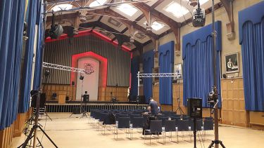 An empty university concert hall rigged up with a stage, sound equipment and lights.