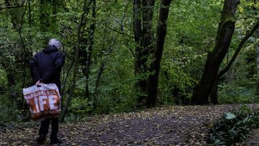 A man with a 'Bargains for Life' bag walks through the woods.