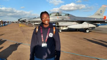 Aerospace student Favour Omolaiye standing in front of a fighter jet