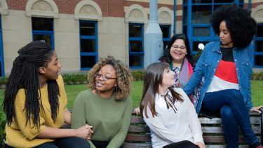 Five female students chat on a bench in the courtyard of the School of Health and Related Research.