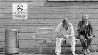 Two people sit and smoke next to a no smoking sign outside a hospital.