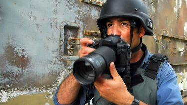 A war journalist prepares to take a photo