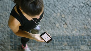 A runner checks a fitness tracking app