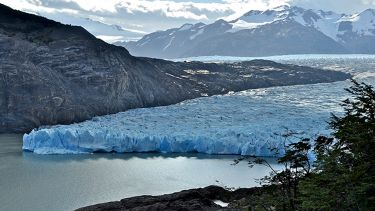 A photograph of glaciers with snowy mountains in the background.