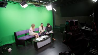 Three students in front of a green screen ready to record a news programme.