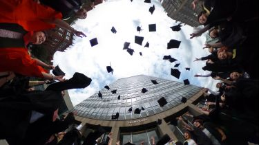 Graduates throwing their mortarboards in the air outside the Arts Tower
