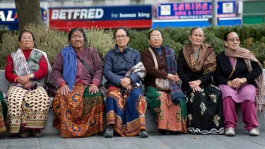 Six women sitting on a public bench