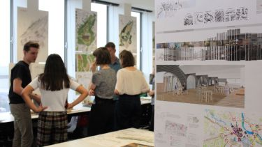 Students gather around concept art in the Department of Landscape Architecture.