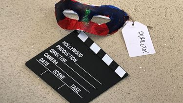A theatrical mask with a tag that says director. There is also a black clapperboard.
