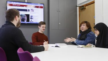A group of politics students have a discussion around a table. BBC News is on in the background.
