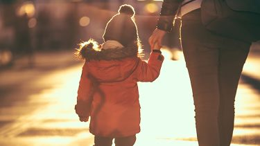 A single parent holds the hand of their young child as they walk down the road.