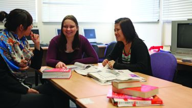 Three female postgraduate students sat at a table looking at a newspaper