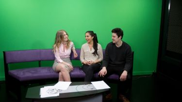 Three masters students learning broadcast skills. They are sitting on a purple sofa in front of a green screen.