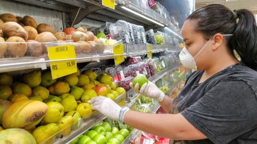 Woman wearing a mask in a supermarket and gloves. She is picking up an apple.